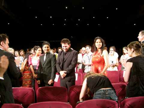 Director Brillante Mendoza flanked by actor Coco Martin (left) and actress Ma. Isabel Lopez (right) while Hollywood director Quentin Tarantino (standing far left) applauds for Brillante.
